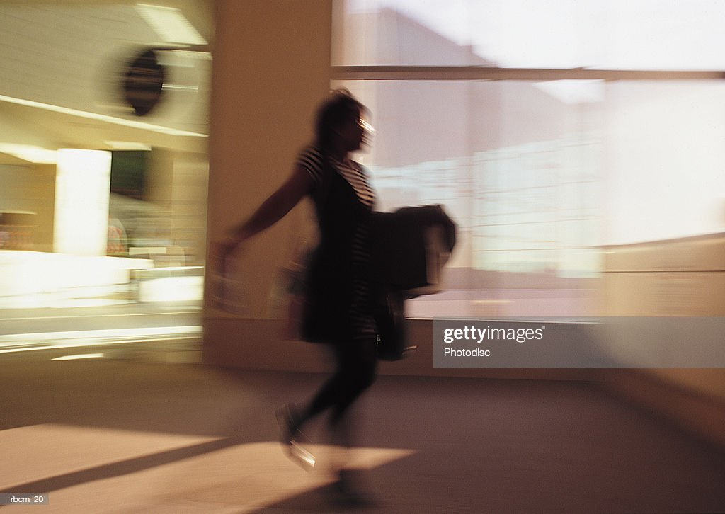 A WOMAN DRESSES IN BLACK RUNS THROUGH AN AIRPORT WHILE CARRYING A BOX : Stockfoto