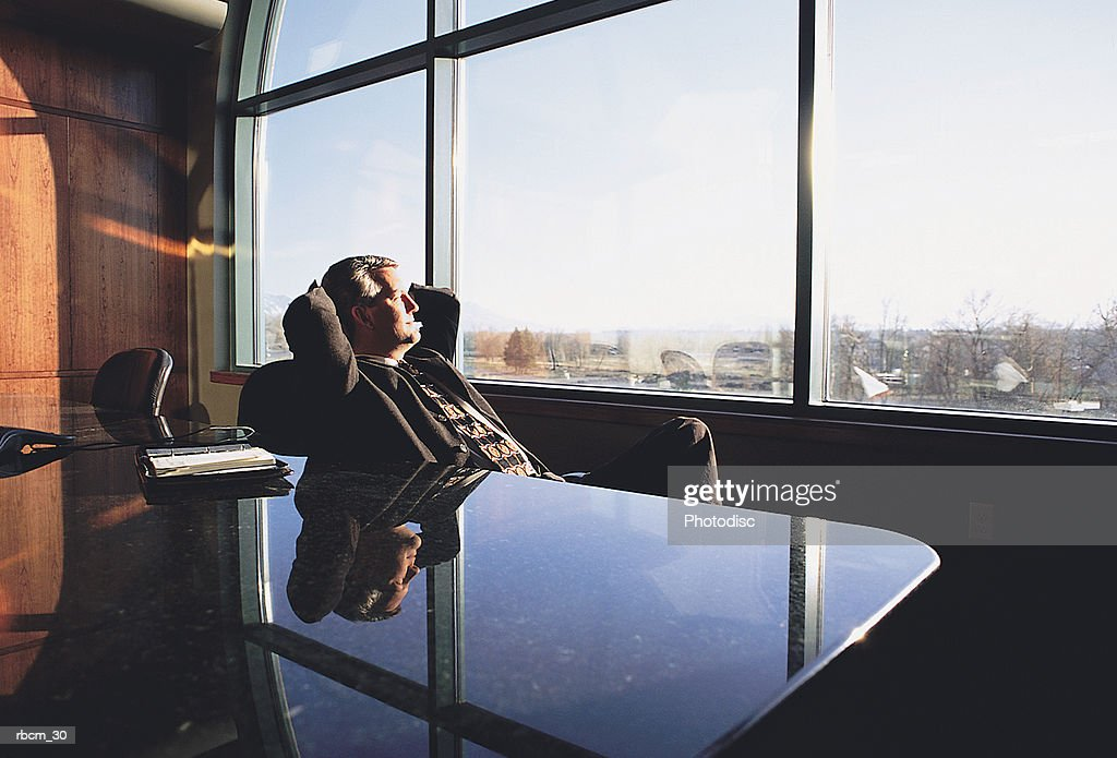 A RELAXED EXECUTIVE IN A SUIT RECLINES IN A CHAIR IN AN OFFICE AS HE LOOKS OUT ON THE CITY : Stockfoto