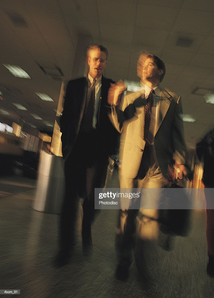 TWO BUSINESSMEN DRESSED IN SUITS TALK AS THEY WALK THROUGH AN AIRPORT CARRYING THEIR BRIEFCASES : Stockfoto