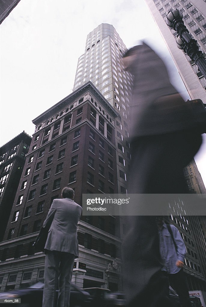 A BLURRED MAN WALKS PAST OTHERS ON A ROAD AMONGST SKYSCRAPERS : Stockfoto