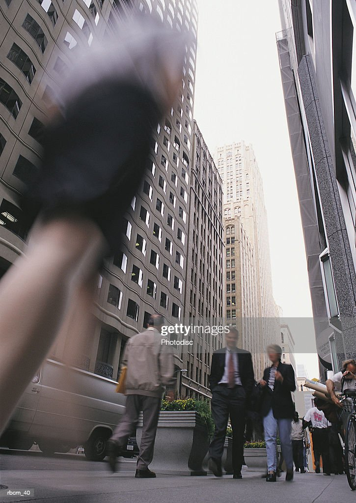A BLURRED WOMAN WALKS ON A POPULATED STREET BETWEEN SKYSCRAPERS : Stockfoto
