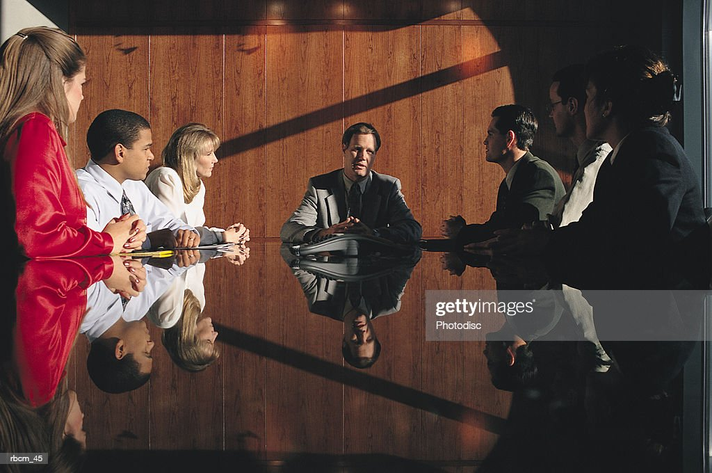 A GROUP OF BUSINESS PEOPLE SURROUND A SHINY CONFERENCE TABLE FOR A MEETING. : Stockfoto