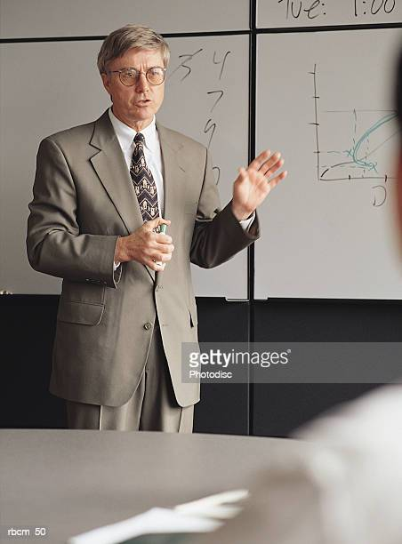 a businessman in a gray suit teaches as he stands by a white board and holds a marker - 背広 ストックフォトと画像