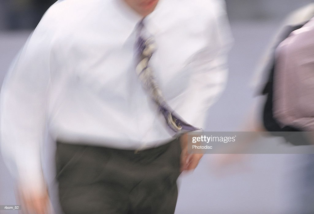 A BLURRED MAN IN A WHITE SHIRT AND TIE WALKS ON A ROAD. : Stockfoto