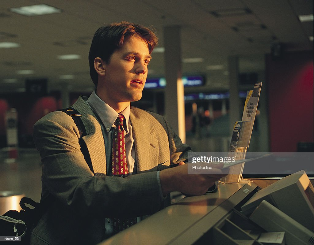 A BUSINESSMAN DRESSED IN A GRAY SUIT HANDS OVER HIS PLANE TICKET WHILE STANDING IN AN AIRPORT : Stockfoto