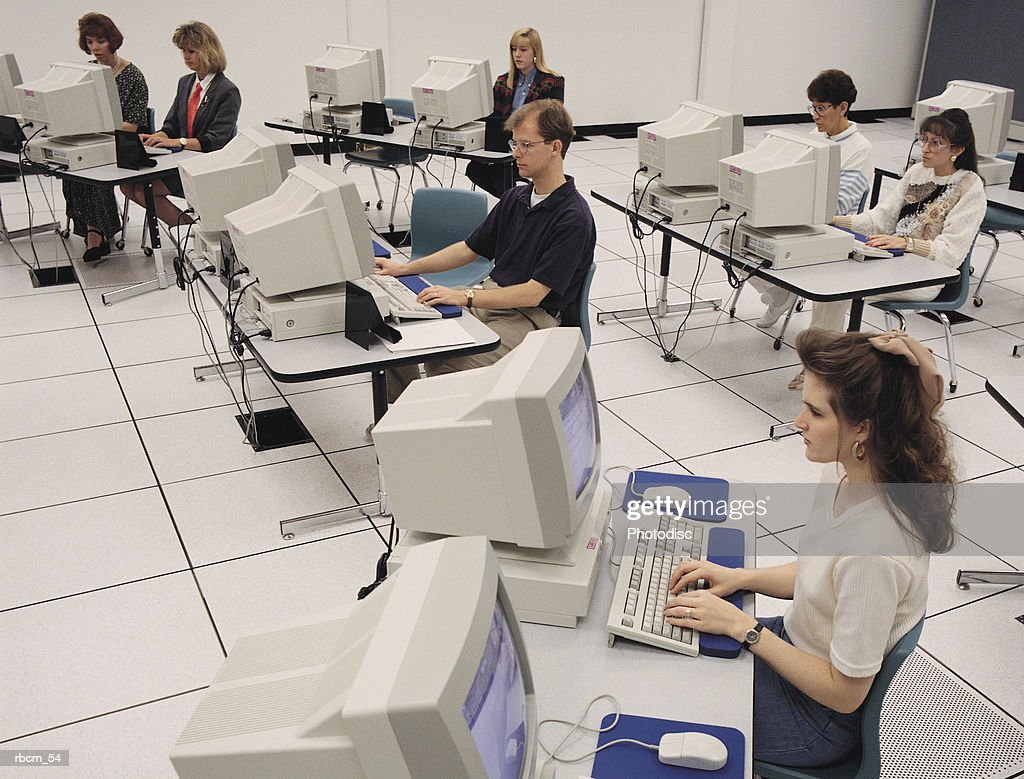 A GROUP OF PEOPLE SIT IN FRONT OF COMPUTERS IN A WHITE ROOM AS THEY LEARN HOW TO USE COMPUTERS : Stockfoto