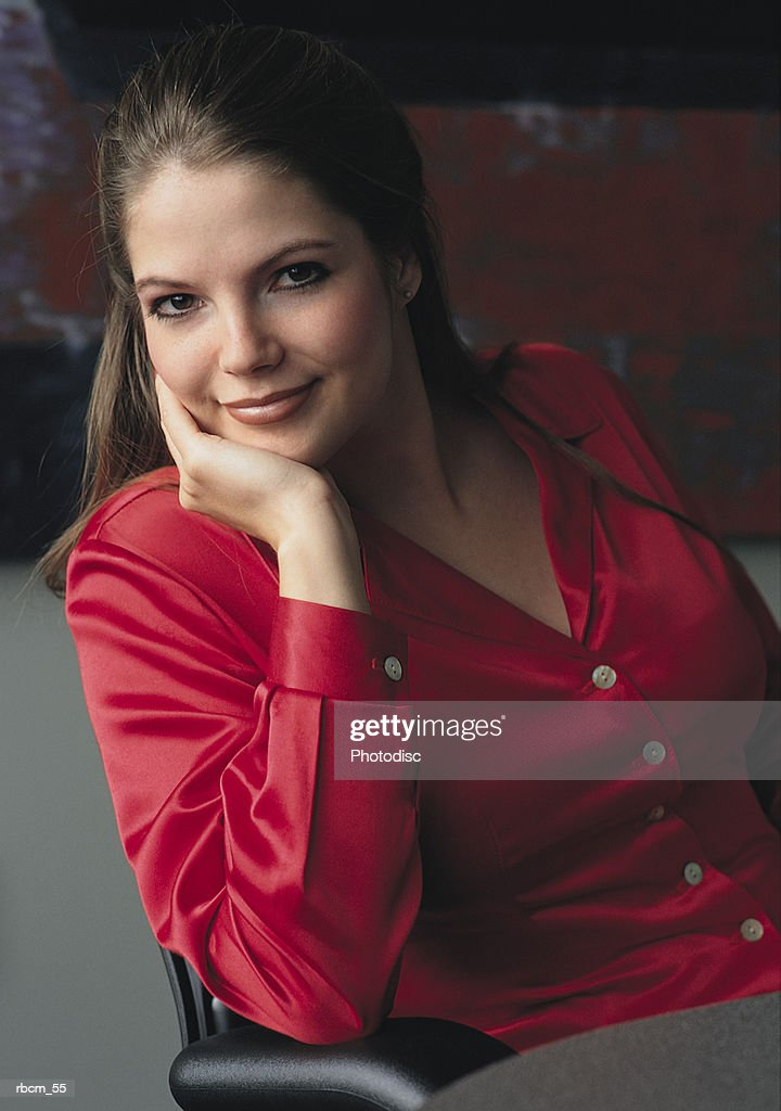 A BUSINESSWOMAN DRESSED IN A RED SHIRT SMILES AS SHE SITS IN A CHAIR : Stockfoto