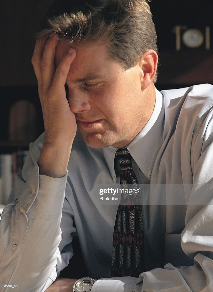 A BUSINESSMAN IN A BLUE SHIRT AND TIE COVERS HIS FACE IN FRUSTRATION : Stockfoto
