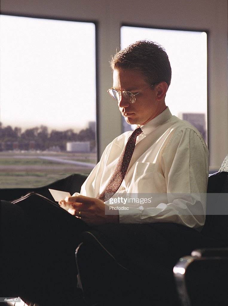 A BUSINESSMAN DRESSED IN A WHITE SHIRT AND BLACK SLACKS READS A LETTER AS HE WAITS FOR A PLANE WHILE IN AN AIRPORT : Stockfoto