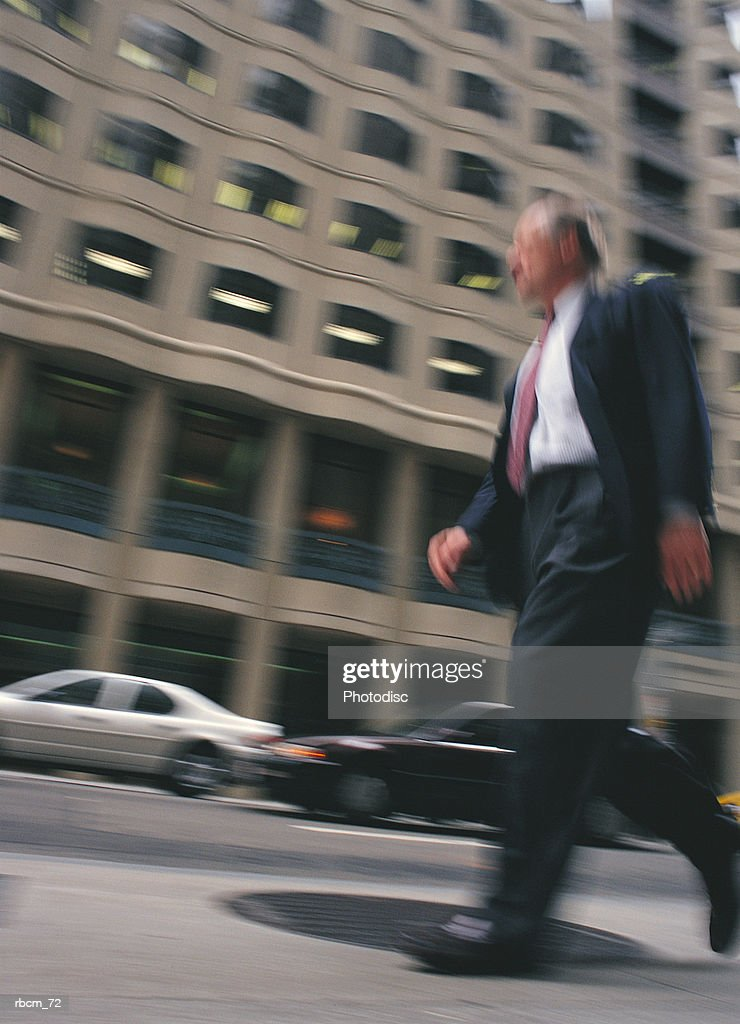 A BUSINESSMAN DRESSED IN A SUIT WALKS ALONG A STREET AMONGST CARS AND BUILDINGS : Stockfoto
