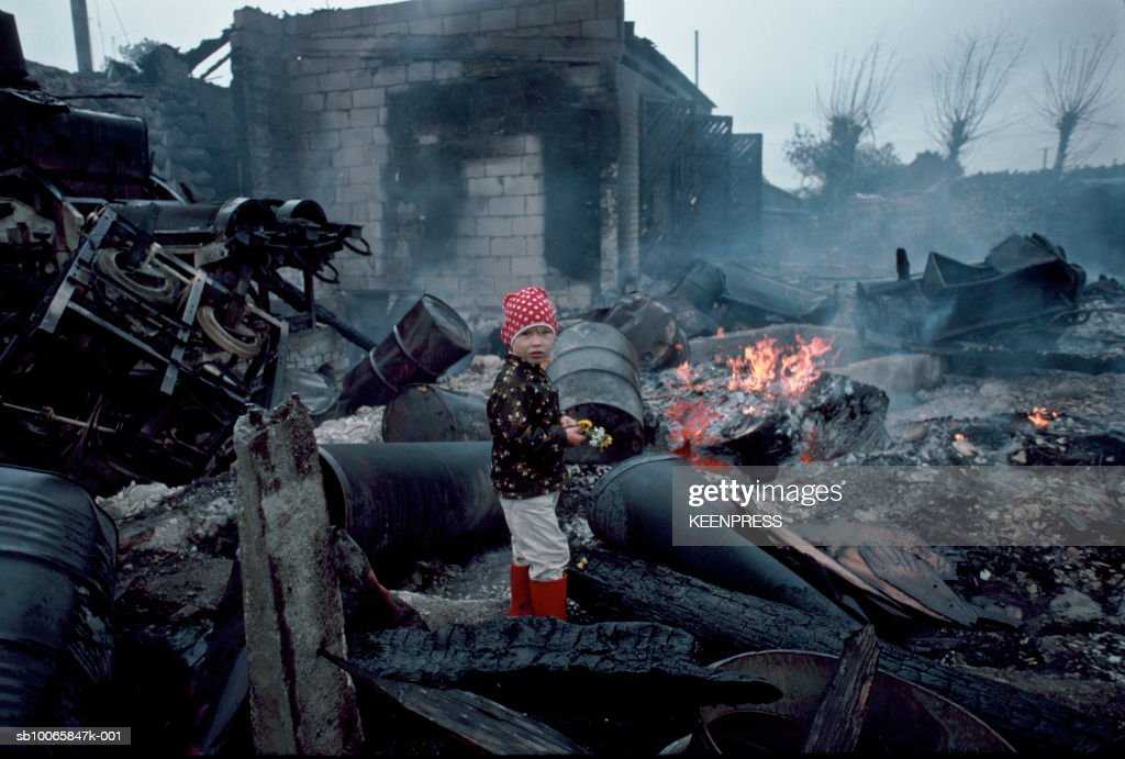Estonia, girl standing in charred rubble and oil drums left over from Soviet occupation in small village : Nachrichtenfoto