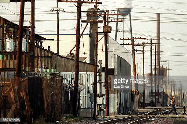 ME0316vernon2LS A woman carries a child as she walks through the industrial landscape of Vernon a community southeast of downtown Los Angeles that...
