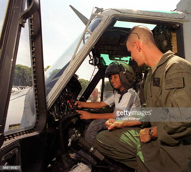 ME0519marine1rk––Alexander Aguilar 8 gets to sit in pilot seat as Sgt Brian Gunther USMC Mag 46Camp Pendletonexplains Twin Huey helicopter at Evans...
