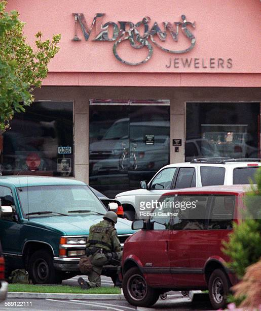 ME0716hostage2RG–A SWAT team member stays low in front of Morgan's Jewelers in the early morning hours Sunday after two armed suspects botched a...