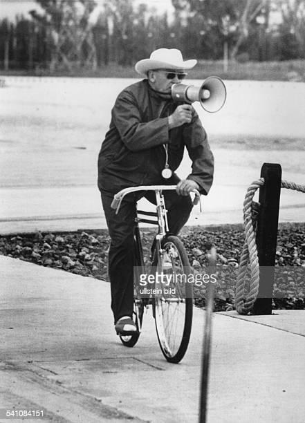 Trainer, Rudern, Pädagoge DOlympische Sommerspiele in Mexiko-Stadt:- fährt auf dem Fahrrad neben derRuderstrecke und gibt mit dem...