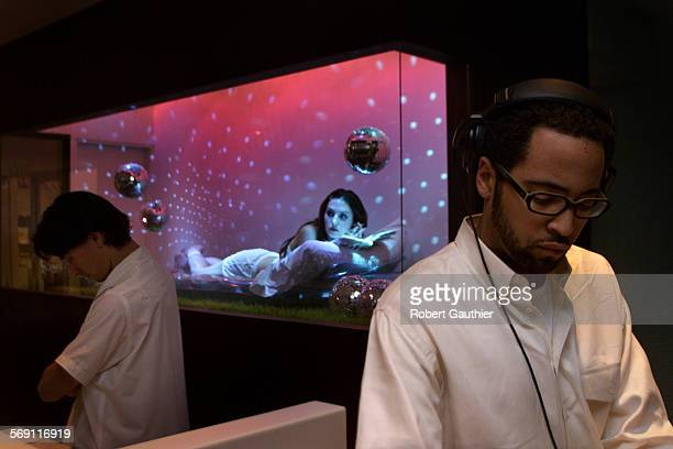 SO0223humanart2RG –– DJ Diallo Riddle tends to his turntable while actress Alice Rogers works her shift in a display case located in the lobby of the...