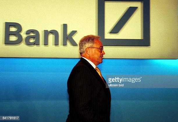 Jurist Bankier DVorstandssprecher der Deutschen Bank Seitenansicht im Hintergrund dasLogo der Deutschen Bank