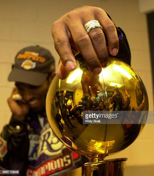 SP0615lakers21WS –– Lakers Kobe Bryant Bryant hangs on to the Championship trophy after defeating the 76ers in Game 5 of the NBA Finals in...