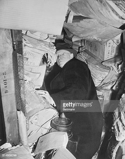 Chief inspector John O'connor of NY Building and Housing Dept conducting a search of the Harlem mansion of Homer and Langley Colyer jamming his way...