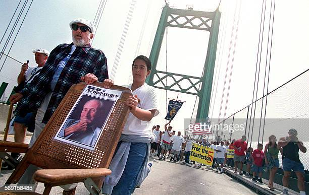 ME0728bridges3WS People walk along the Vincent Thomas Bridge in San Pedro carrying a picture of Harry Bridges during a labor march celebration...