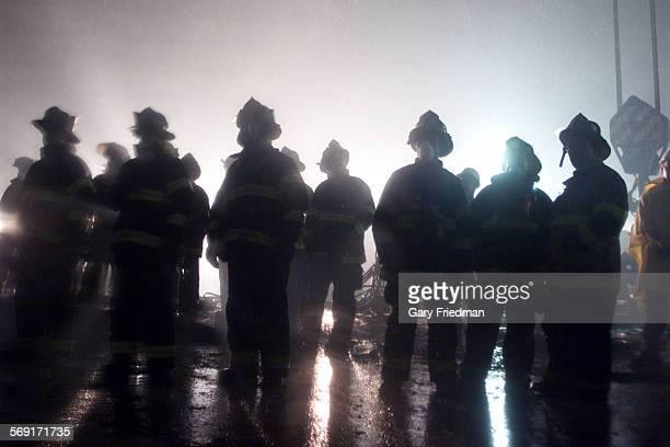 035890me0914warzone3gf Firefighters watching rescue workerslook for survivors at the World Trade Center in the early morning hours on Sept 14 2001