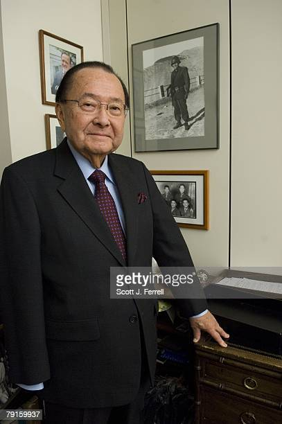 Senate Appropriations Defense Subcommittee Chairman Daniel K. Inouye, D-Hawaii, in front of a picture of himself in France as a U.S. Soldier during...