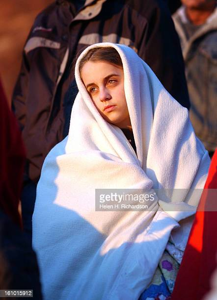 04_20_03_cd21sunrise13 year old Christy Hart of Lakewood looking rather religious wrapped up in her white blanket keeps warm while watching the sun...