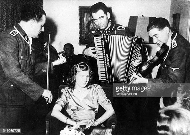 *Lebensgefährtin Adolf Hitlersmit drei Musikern in SSUniform die anlässlich der Hochzeit ihrer Schwester Gretl mit Hermann Fegelein spielen 1944