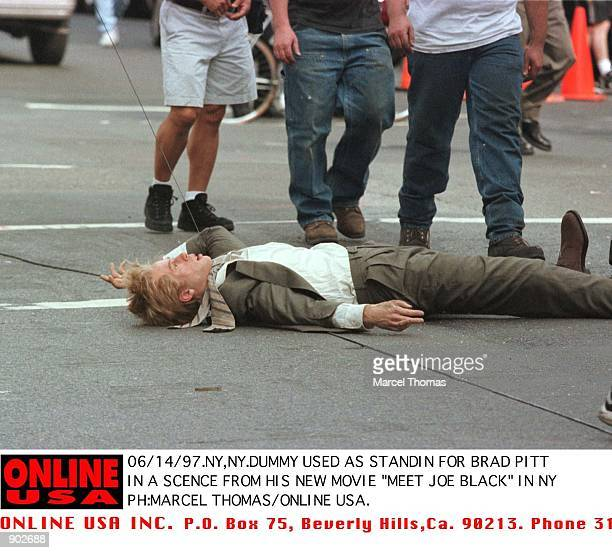 Dummy used as stand in for Brad Pitt in scence from his new movie 'Meet Joe Black' lies at the feet of extras after it was struck by a taxi