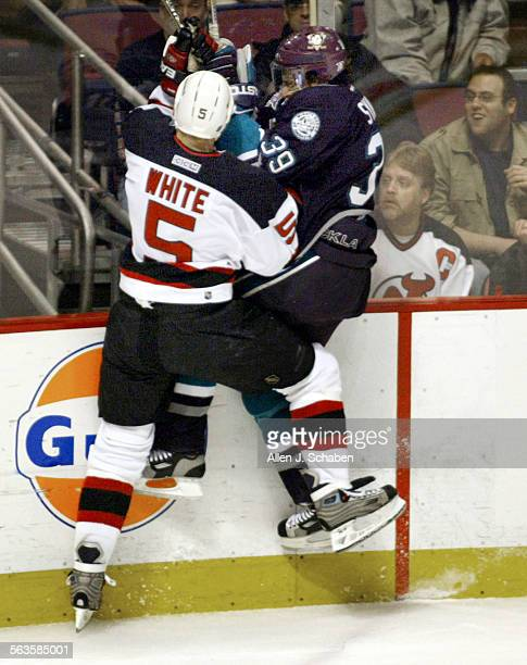 SP0527ducksAJS––Anaheim's Petr Sykora gets checked on the boards by New Jersey's Colin White in the second period of game one of the Stanley Cup...