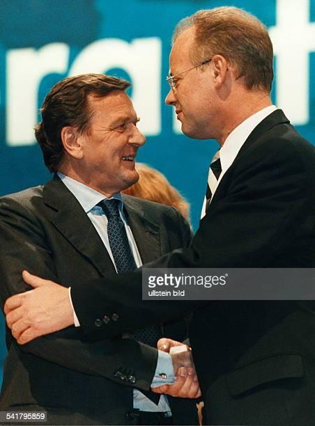 Politiker SPD DBundeskanzler Schröder und derBundesverteidigungsminister RudolfScharping schütteln sich die Hände April 1999