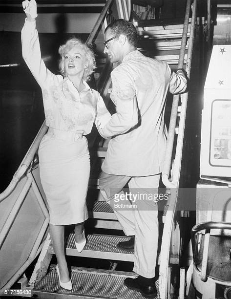 With her husband Arthur Miller holding her arm actress Marilyn Monroe with silver threads instead of goldis shown as she waved goodbye to New York...