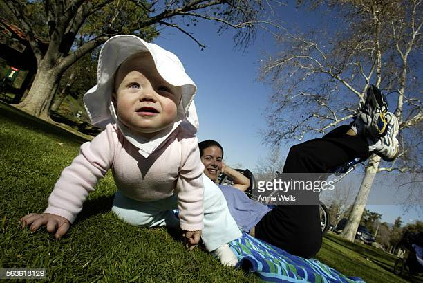HE0212fitnes Ella Onderdonk 8 mos crawls away from her mom Katrina Onderdonk while mom does sit–ups This is for a fitness bound columnon a...