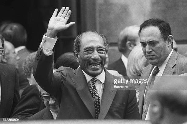 Egyptian President Anwar Sadat waves to crowd as he and David Rockefeller arrive at the Council on Foreign Relations lunch here 8/7 BPA2
