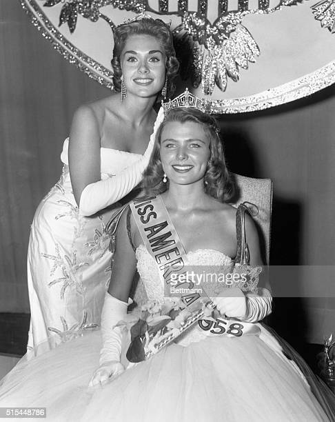 Atlantic City, NJ- Miss Colorado waits as Miss America, Marian Ann Mcknight, places the crown on her head after she was named Miss America 1958...