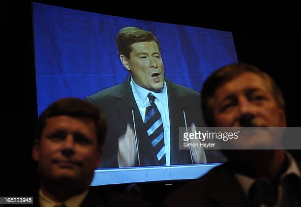 Stephen Harper and Mike Harris frame candidate John Tory on a video screen as he addresses crowd at the Ontario Conservative leadership debate in...