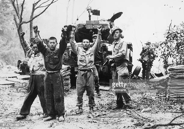 South Korea Helmet set at a jaunty angle this US Marine orders captured North Koreans to keep their hands up In the background is one of the tanks...