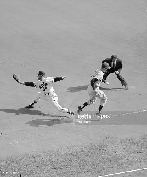 Milwaukee,WI: Tony Kubek of NY Yankees, crosses first base beating throw to Braves' first baseman Frank Torre by pitcher Warren Spahn in first inning...
