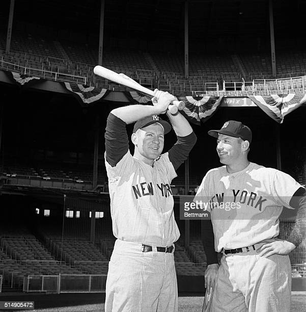 New York NY Yankee pitcher Whitey Ford swings a couple of bats under the watchful eye of Yankee slugger Mickey Mantle at an early morning workout in...