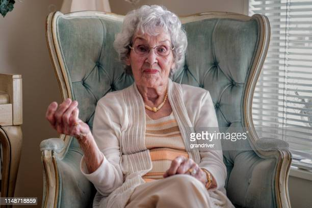 100-year old woman having a cheerful conversation in her home - 90 plus years stock pictures, royalty-free photos & images