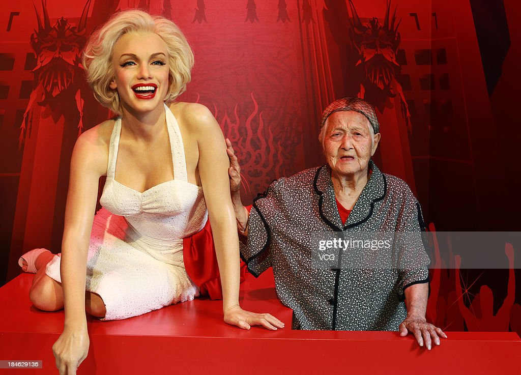 100-year-old Wen Gaishuan poses with a wax figure of Marilyn Monroe at Madame Tussauds on October 11, 2013 in Wuhan, China. Wuhan Evening News and Huaxia Qianqiu Education Foundation selected ten healthy centenarians in Wuhan city, and invited them to visit the Madame Tussauds to celebrate the Double Ninth Festival.