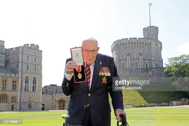 100yearold WWII veteran Captain Tom Moore poses with his medal after being made a Knight Bachelor during an investiture at Windsor Castle in Windsor...