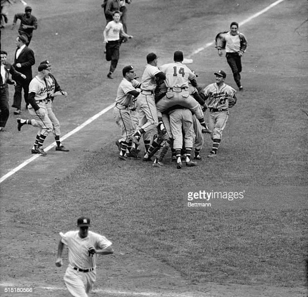Frank Torre 'rides' Milwaukee Braves' victory pitcher Lew Burdette as the rest of the club crowds around after the Braves beat the New York Yankees...