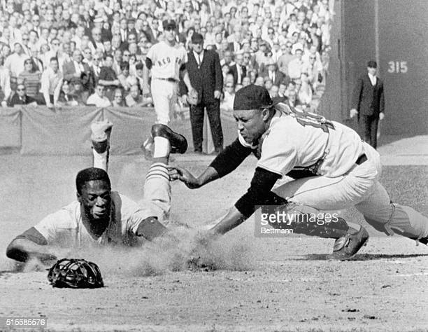 Lou Brock of the Cardinals dives safely into home plate in the third inning of the sixth World Series game as Red Sox catcher Elston Howard lunges in...