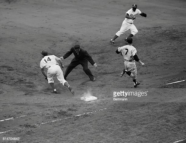 New York, NY: Mickey Mantle, Yankees, beats out a bunt in the fourth inning of the last game of the World Series played at Ebbets Field. Gil Hodges...