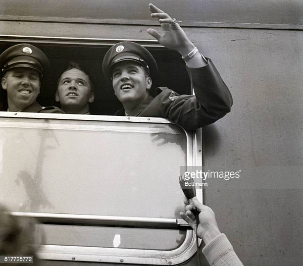 Bremerhaven, Germany: Private Elvis Presley of rock 'n' roll fame looks from a train window with two other GI's and waves to fans who greeted him on...