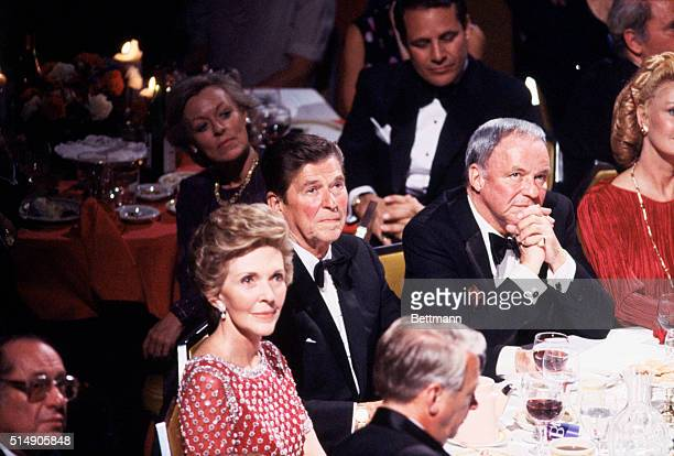 New York, NY: Ronald Reagan and wife, Nancy, huddle with Frank Sinatra at the Waldorf 9/30. The Waldorf get together was part of a nationwide tribute...