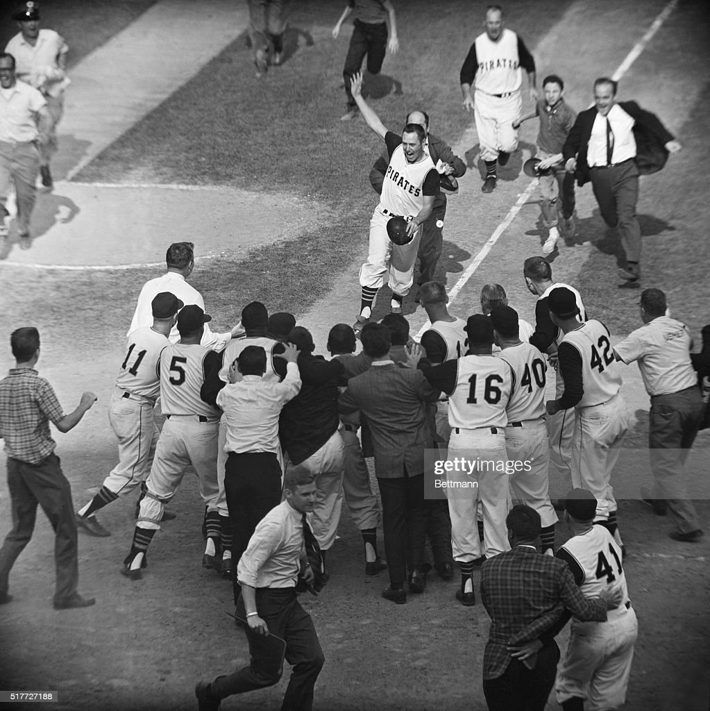 Pirate Bill Mazeroski chased by a fan gets ready to cross home plate and is greeted by fans and fellow players after his ninth inning homer in the World Series.