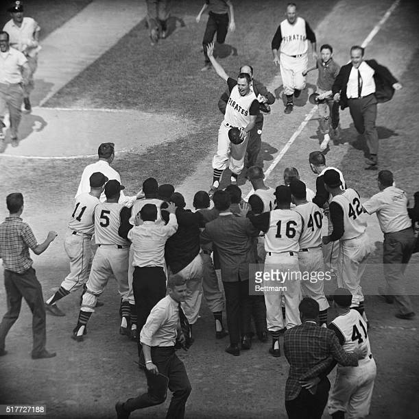 Pittsburgh, PA: Pirate Bill Mazeroski chased by a fan gets ready to cross home plate and is greeted by fans and fellow players after his ninth inning...