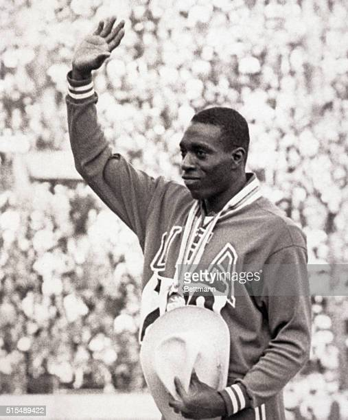 Tokyo Japan America's Bob Hayes winner of the gold medal in the Olympic 100meter dash is flanked by silver medalist E Figerola of Cuba and bronze...